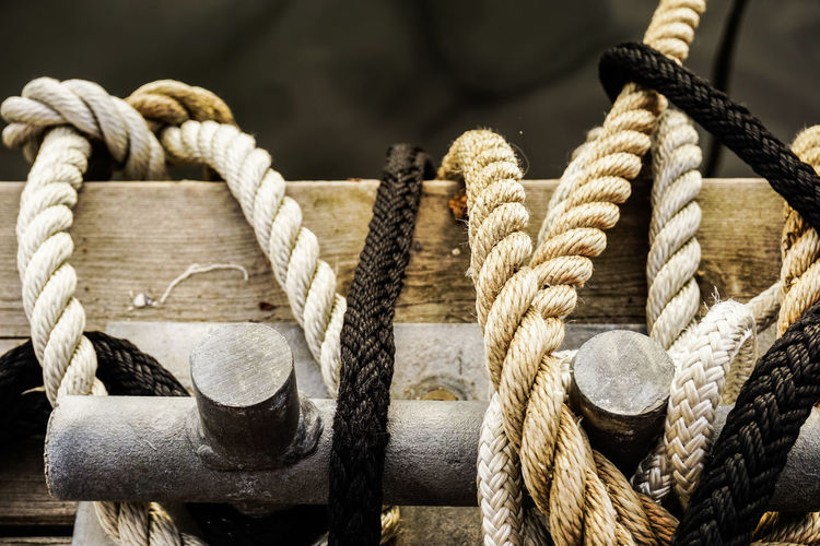 Close-up of ropes tied on wooden boat on river