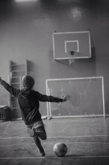 Rear View Of Young Boy Playing Soccer In Sports Hall