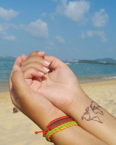 Female hands against sea in summer