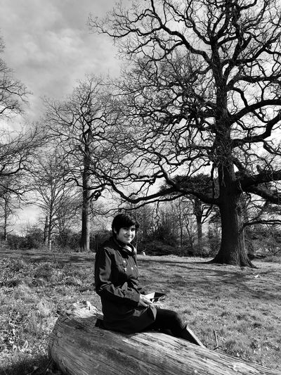 Man sitting on field against trees
