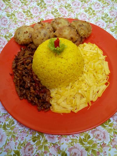 Yellow rice, roll eggs, tempe and fried mashed potatoes. Traditionalfood Indonesianculinary