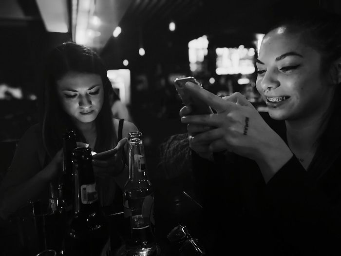 Smiling friends using phones by bottles on table in nightclub