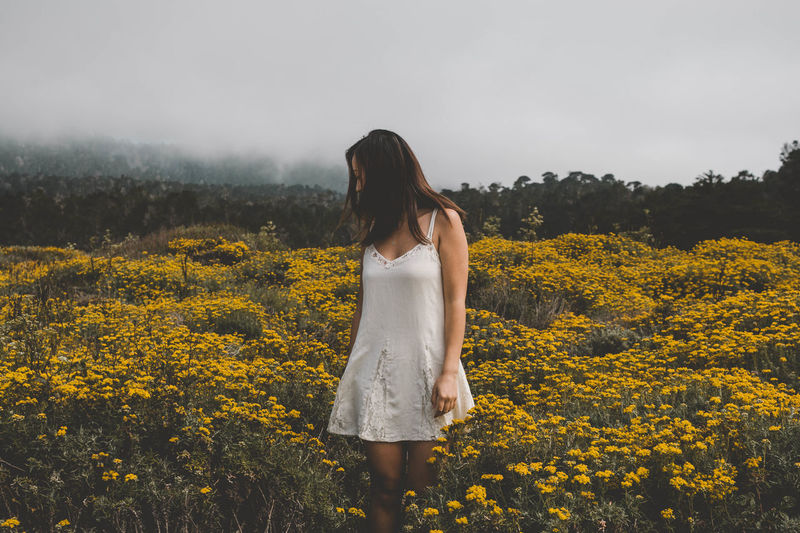 Young woman standing amidst yellow flowers on field