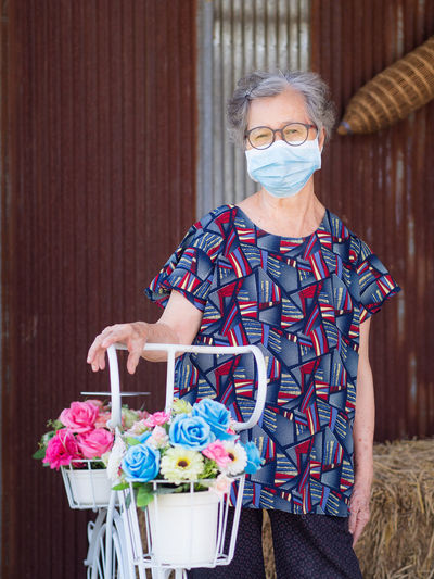 Elderly woman wearing a face mask looking at camera while standing side a flowers bicycle