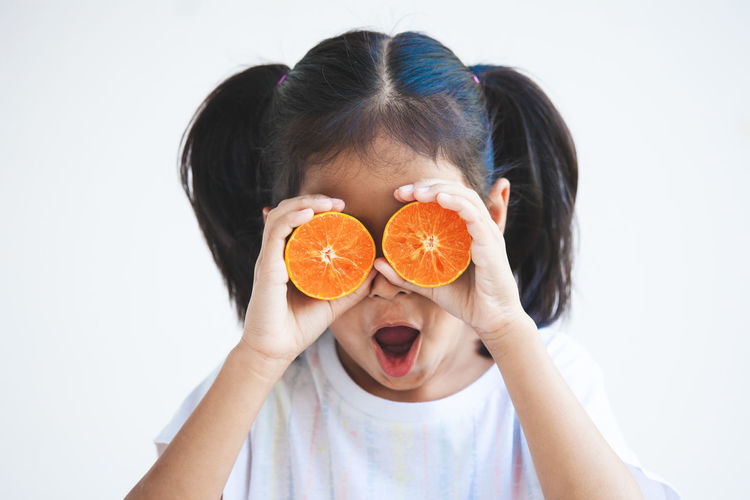 Close-up of girl holding orange over eyes