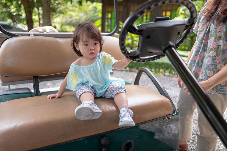 Midsection Of Woman Standing By Daughter Sitting On Golf Cart