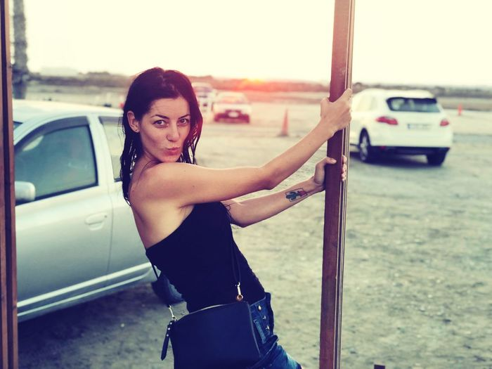 Portrait Of Smiling Woman Standing By Car