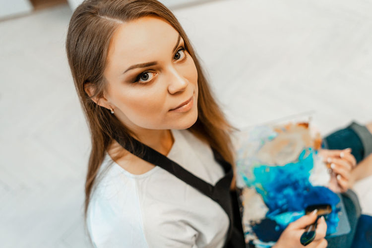 High angle portrait of woman holding canvas at home