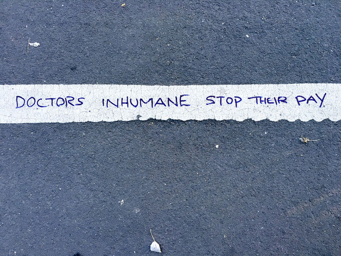 Message written on white line on the pavement in marker pen Asphalt Close-up Complaint Day Expressing Graffiti Message No People Outdoors Pavement Protest Road Road Marking Sidewalk Statement Text Urban Western Script