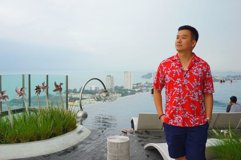 Young man looking away while standing against infinity pool