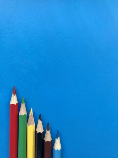 Close-up of colored pencils against blue background