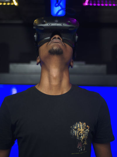 Young Adult Virtual Reality Simulator Gamer Device Technology Communication One Person Front View Real People Leisure Activity Lifestyles Indoors  Young Men Casual Clothing Men Portrait Focus On Foreground Sport Standing Waist Up Blue Headshot Illuminated Nightlife