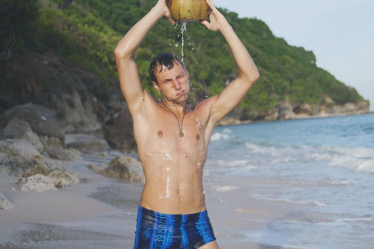 Shirtless mid adult man bathing with coconut water at beach