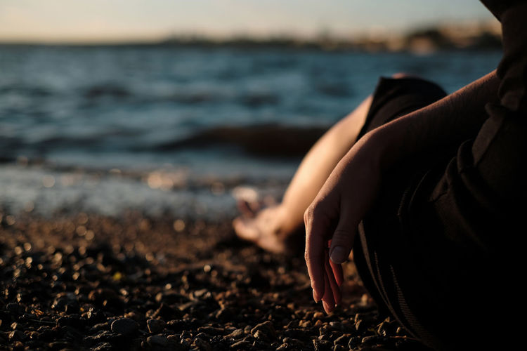 Midsection of person on beach against sea