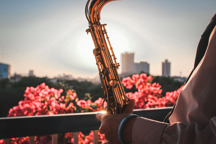 Midsection of girl playing saxophone in city against sky