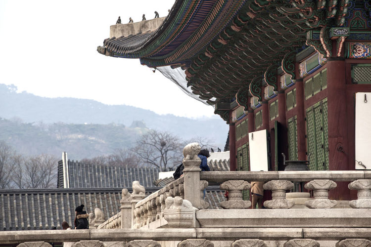 Architecture Building Exterior Built Structure Day Famous Place Famous Places Gyungbok Palace Historic Building History Korean Traditional Palace Mountain Mountain Range Place Of Worship Real People Religion Roof Roof Sky Spirituality Temple - Building Tourism Travel Travel Destinations Tree