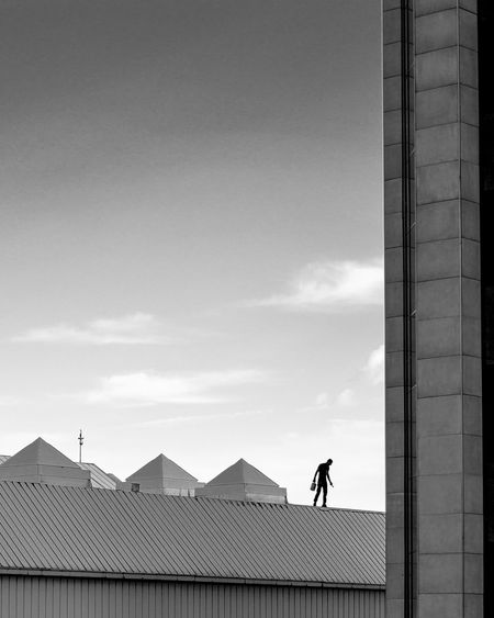 Silhouette man standing on building roof against sky