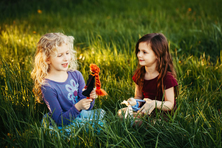 Happy children girls playing dolls in park. happy childhood authentic lifestyle. outdoor summer