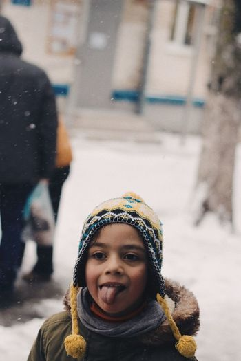 Girl Sticking Out Tongue While Standing Outdoors During Winter