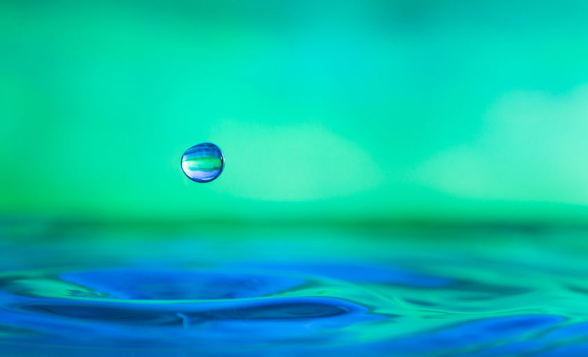 Close-up of drop falling on water surface against turquoise background