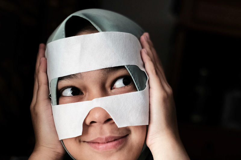 Close-up of woman with face covered by tape against black background