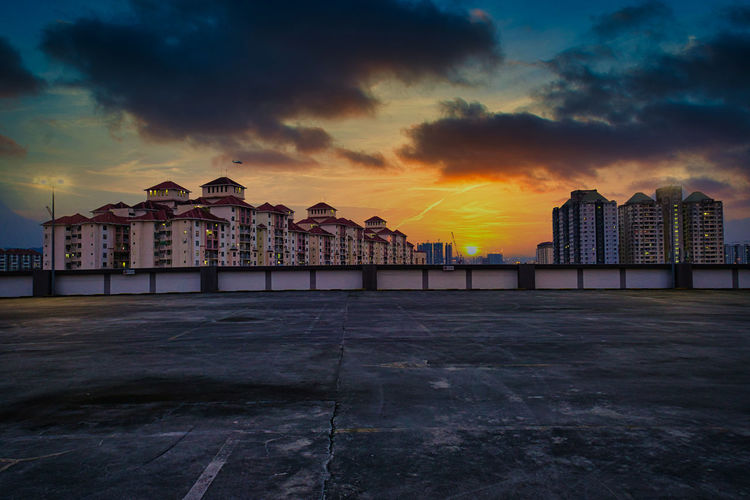 View of buildings against cloudy sky at sunset