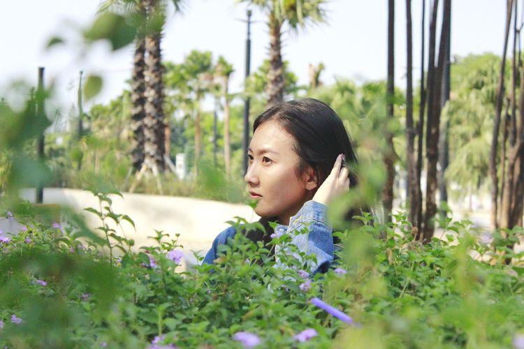 Portrait of girl looking at flowering plants