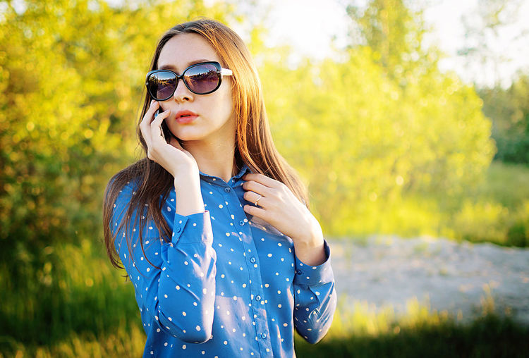 Young woman wearing sunglasses standing outdoors