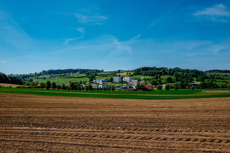 Farm Field By Residential District On Hill Against Blue Sky
