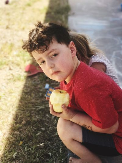 Portrait of boy with sister holding apple on field