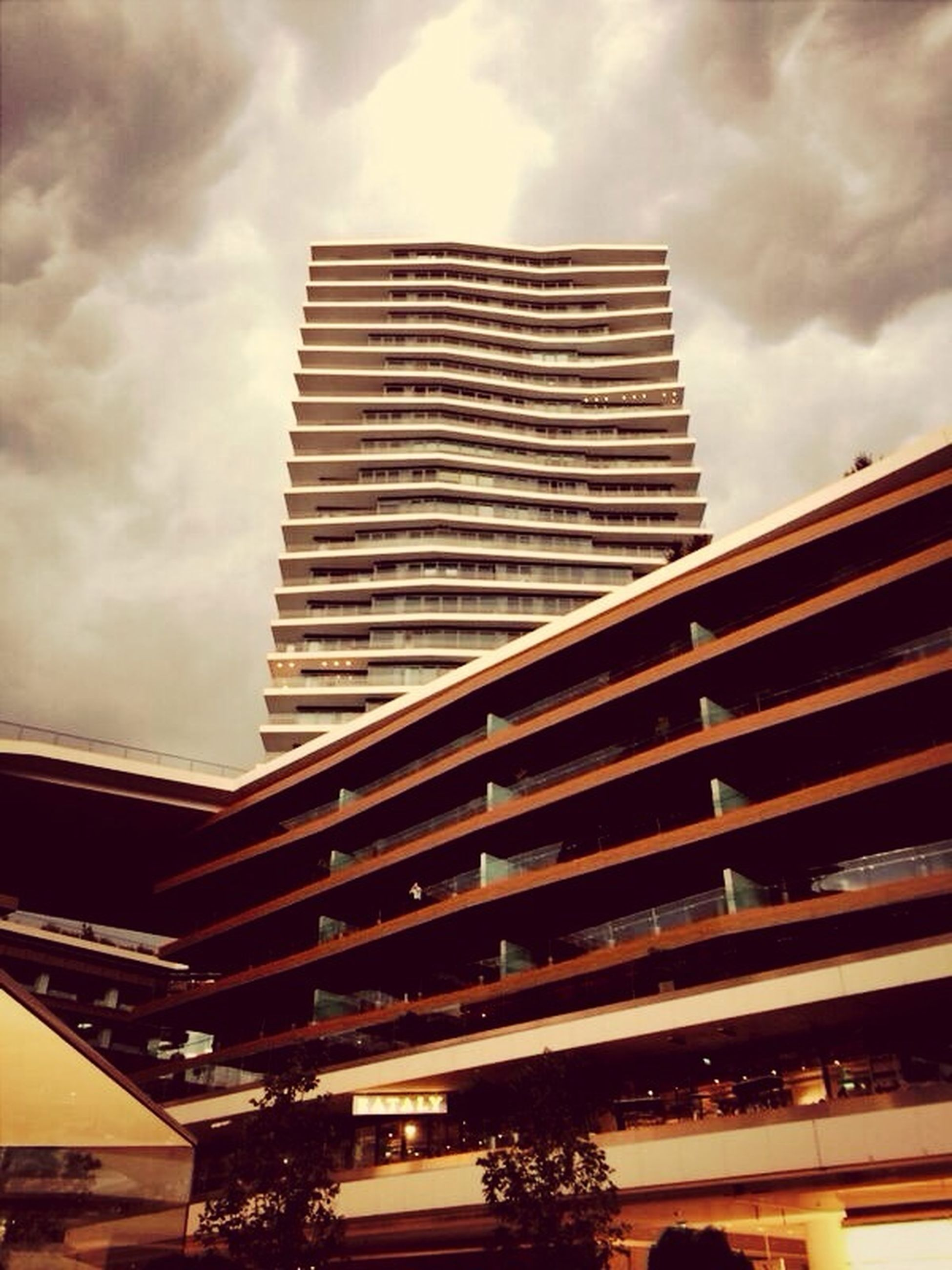 low angle view, architecture, built structure, building exterior, sky, cloud - sky, cloudy, modern, cloud, building, city, skyscraper, office building, outdoors, tall - high, no people, overcast, day, roof, tower
