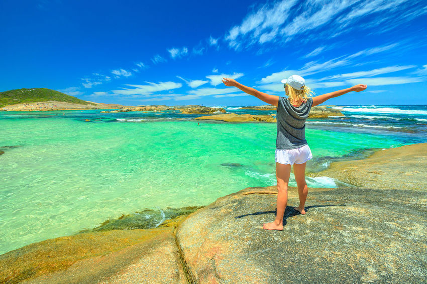 Happy woman with open arms looking the calm turquoise waters of Greens Pool in William Bay National Park, Denmark, Western Australia. Blonde young girl standing on the huge boulders on a summer day. Australia Western Australia Beach Sea Sea And Sky Sunbathing Sand Shore Boulder Blue Sky People Tourist Travel Destinations Summer Madfish Beach William Bay National Park Elephant Rocks Greens Pool Coastline Ocean View Waterfall Beach Denmark Woman Girl Female Water Full Length One Person Leisure Activity Sky Lifestyles Human Arm Casual Clothing Nature Limb Standing Beauty In Nature Scenics - Nature Women Trip Vacations Real People Arms Outstretched Arms Raised Outdoors Turquoise Colored