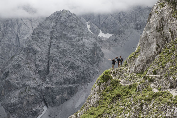 Hikers Standing At The Edge Of Ehrwalder Sonnenspitze