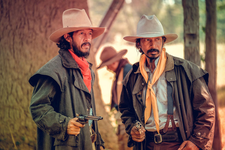 Cowboys with guns standing on land