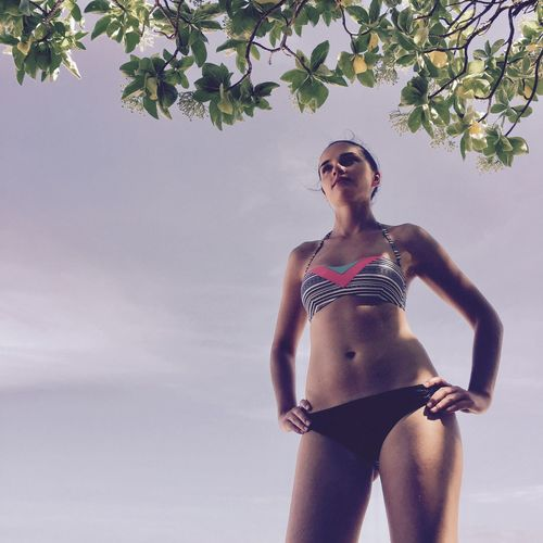Low angle view of sensuous woman in bikini standing against sky