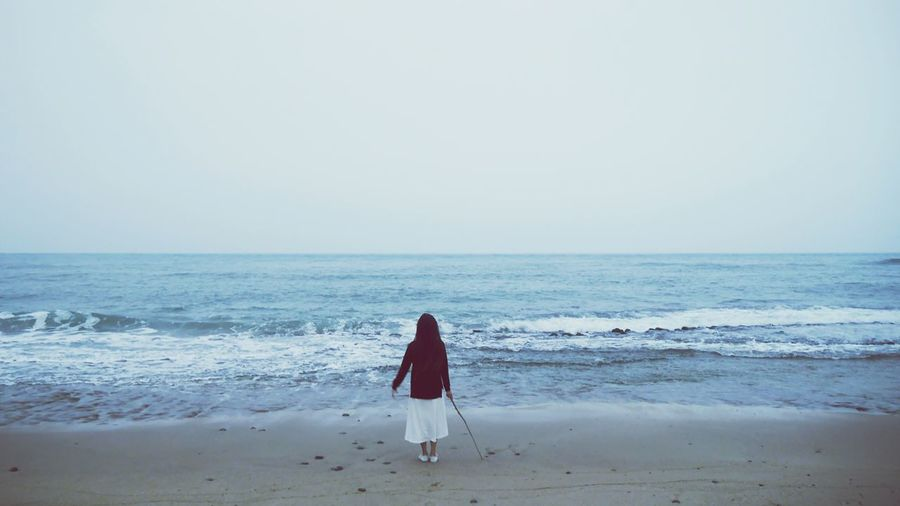 Rear View Of Woman Wearing Hood While Standing At Beach Against Sky