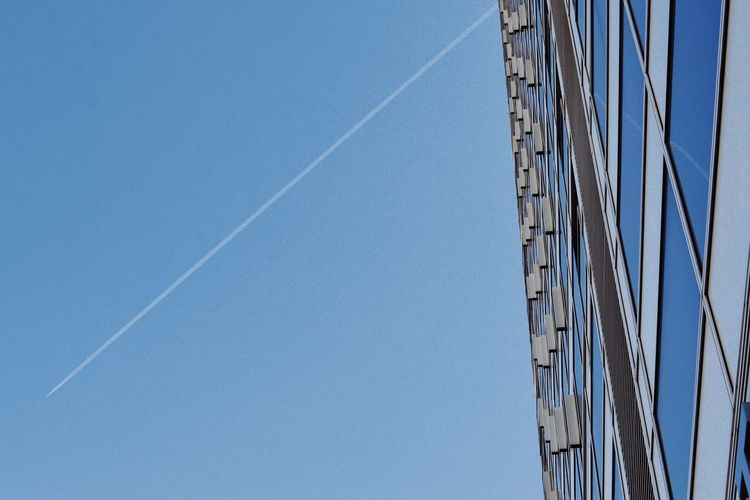 Sky Low Angle View Vapor Trail Blue Clear Sky No People Day Nature Built Structure Copy Space Architecture Building Exterior Transportation Outdoors Building Mode Of Transportation Sunlight Tall - High Skyscraper Directly Below 17.62° My Best Photo