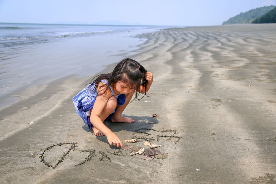 Cute girl in 6 years old wearing blue dress was writing english alphabet on the sand at the sea shore at Laem Son National Park, Ranong, Thailand Beach Beauty In Nature Casual Clothing Childhood Day Full Length Girl Horizon Over Water Kid Leisure Activity Lifestyles Nature One Person Outdoors People Real People Sand Sand Dune Sand Pail And Shovel Sea Shore Sky Water Summer Exploratorium