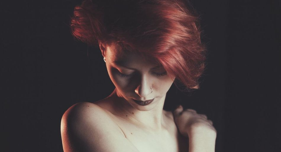 Close-up of redhead woman over black background