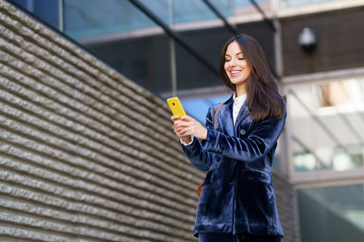 Full length of woman holding smart phone while standing outdoors