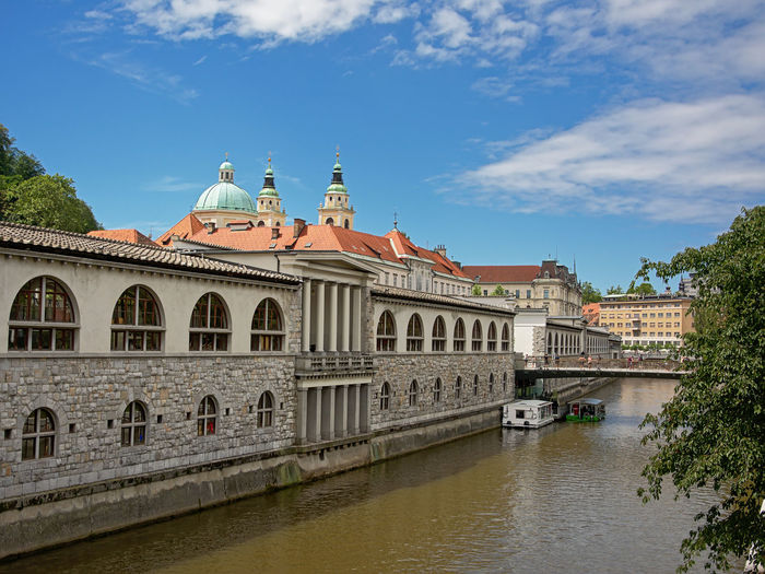 Ljubljana neoclassical central market building, designed by Jose Plecnik, view from across river Ljubljanica, with towers of the cathedral in the back Cathedral City Ljubljana Market Market Hall Plečnik Slovenia Tourist Architecture Bridge$ Building Exterior Built Structure Classical Dome Europe Historical History Jose Plcnik Neoclassical No People River Sky Tourism Travel Destinations Water