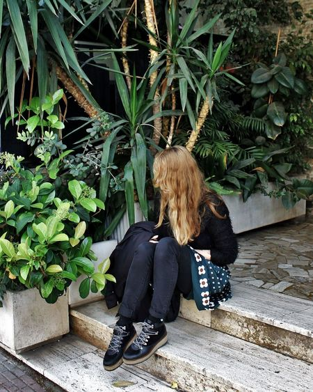 Woman Sitting On Steps By Plants