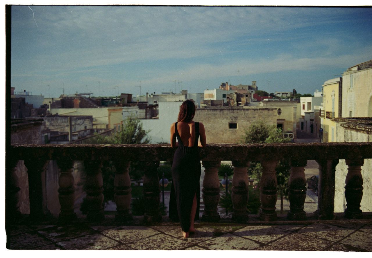 WOMAN STANDING BY CITYSCAPE