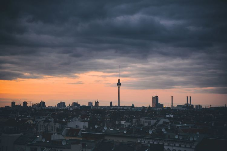 Fernsehturm Tower With Cityscape Against Cloudy Sky At Dusk