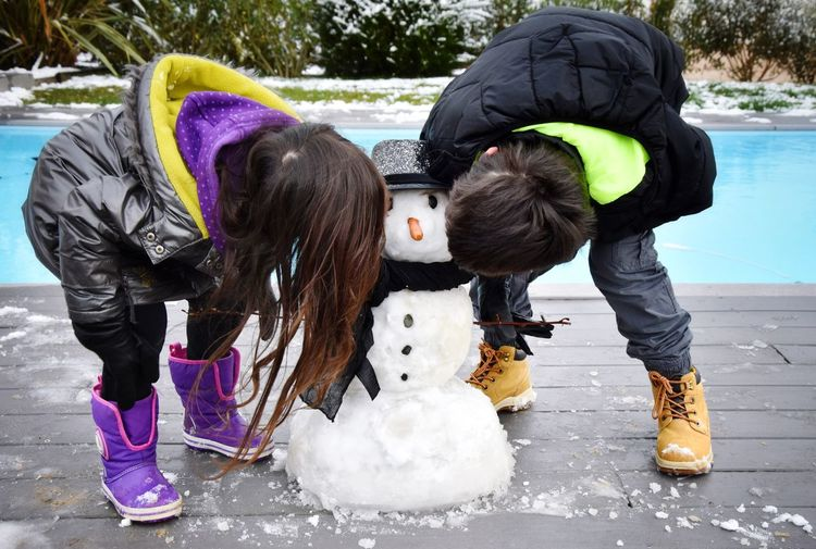 Siblings Kissing Snowman At Poolside