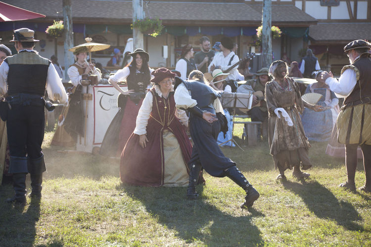 A costumed man and woman dance at a Renaissance Festival in Minnesota 17th Century Afternoon Dance Dancing Lady Minnesota Old Fashioned Renaissance Festival Sunlight USA Back Lit Bowing Celebration Dust Entertainment Gentleman  Editorial  Historical Men Musician Partner Real People Shadow Vintage Women