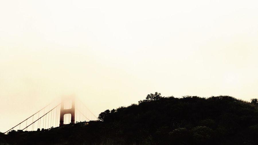 Suspension bridge against cloudy sky