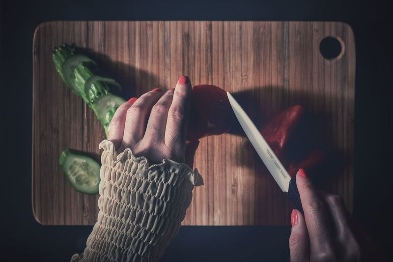 Midsection of woman holding vegetables on cutting board