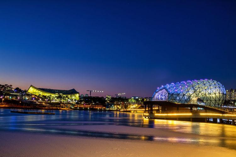 Illuminated city by sea against blue sky at night