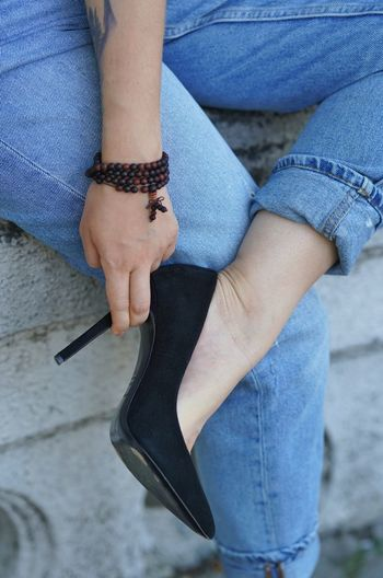 Low section of woman wearing shoe